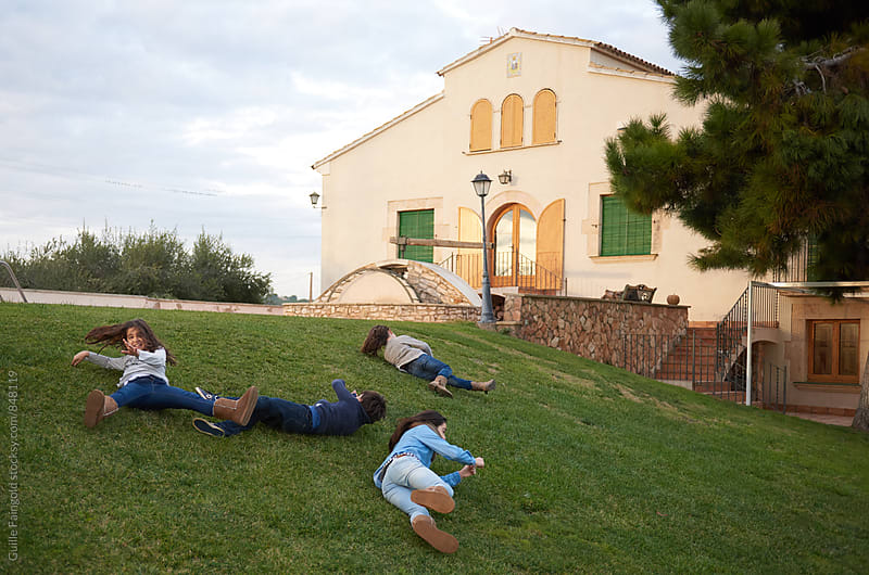 Children rolling on lawn by Guille Faingold for Stocksy United
