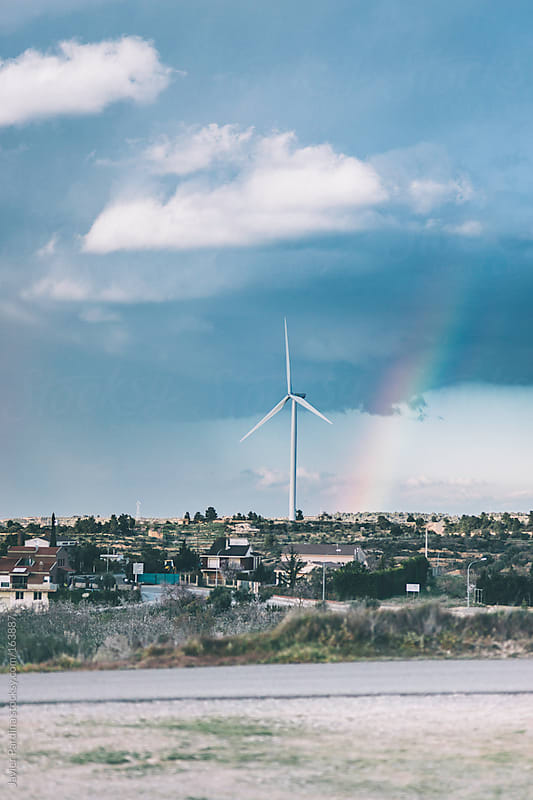 landscape of rural town with a  windmill and a rainbow by Javier Pardina for Stocksy United
