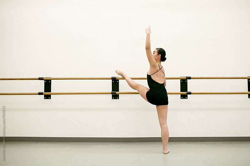 Woman stretching on ballet bars  by Jennifer Brister for Stocksy United