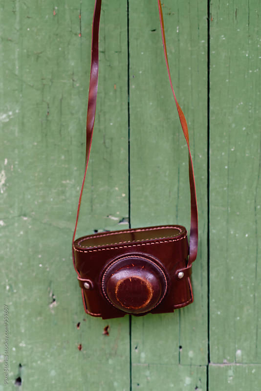 Vintage film camera hanging on wall by Pixel Stories for Stocksy United