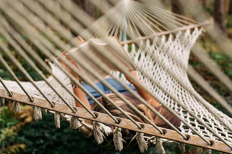 Woman reading in a hammock by Gabriel (Gabi) Bucataru for Stocksy United