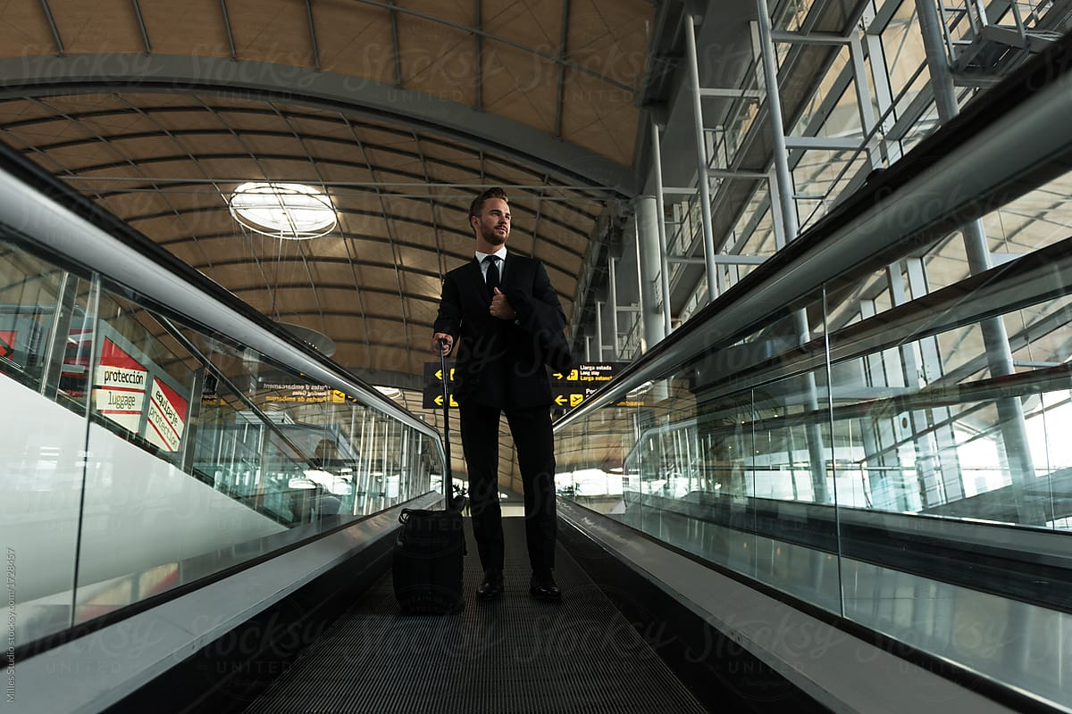 Stylish Entrepreneur On Moving Stairs In Airport By Milles Studio For  Stocksy United