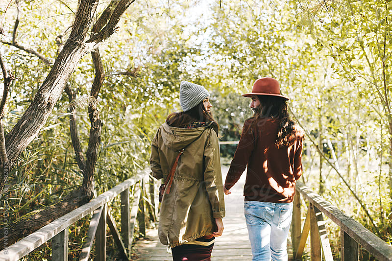Back view of couple walking on a wooden bridge in the forest. by BONNINSTUDIO for Stocksy United