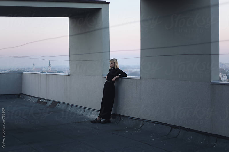 Stylish woman standing on the roof of the building during sunset by VeaVea for Stocksy United