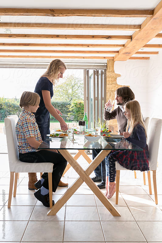 Lunch with a family sitting in a bright modern dining area of a timber framed house. by Paul Phillips for Stocksy United
