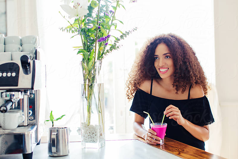 Portrait of a curly beautiful woman holding a fresh smoothie in a coffee shop. by BONNINSTUDIO for Stocksy United
