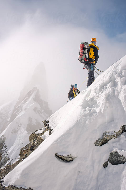 Mountaineers climbing snow covered mountains by RG&B Images for Stocksy United