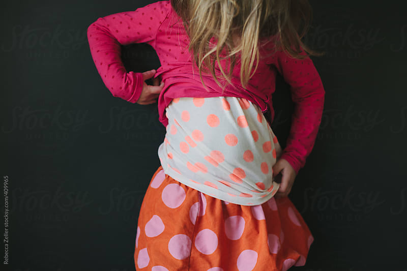 A girl with layers of polka dots examines her outfit by Rebecca Zeller for Stocksy United