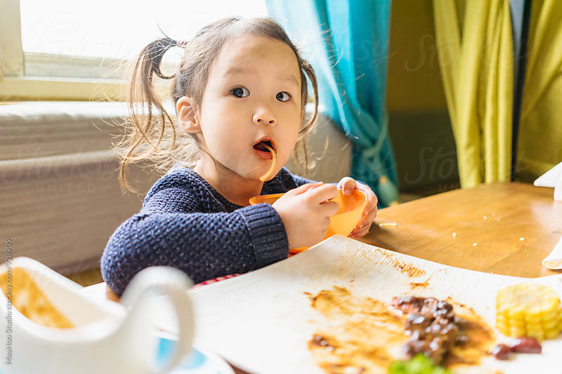 Toddler girl sitting in restaurant and eating spaghetti by Maa Hoo for Stocksy United