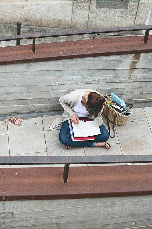 Beautiful young student woman writing on notebook sitting on the street. by BONNINSTUDIO for Stocksy United