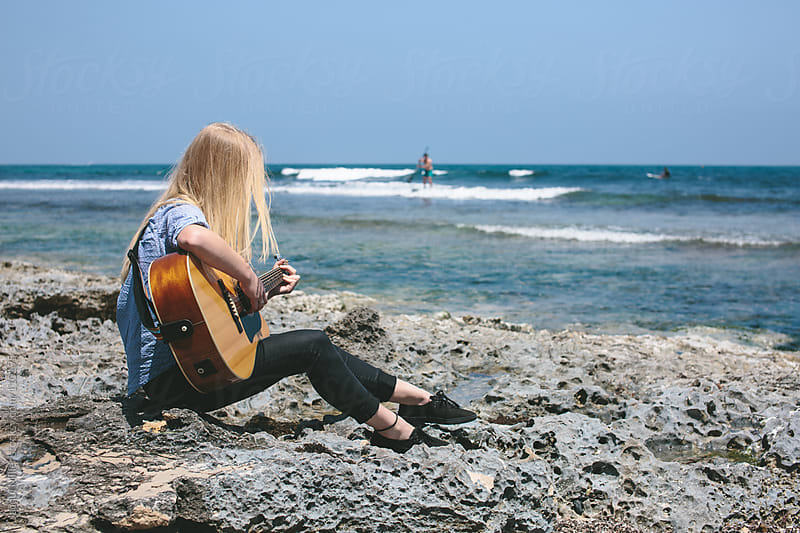 Girl sits on rocks at the beach with her guitar by Jacqui Miller for Stocksy United