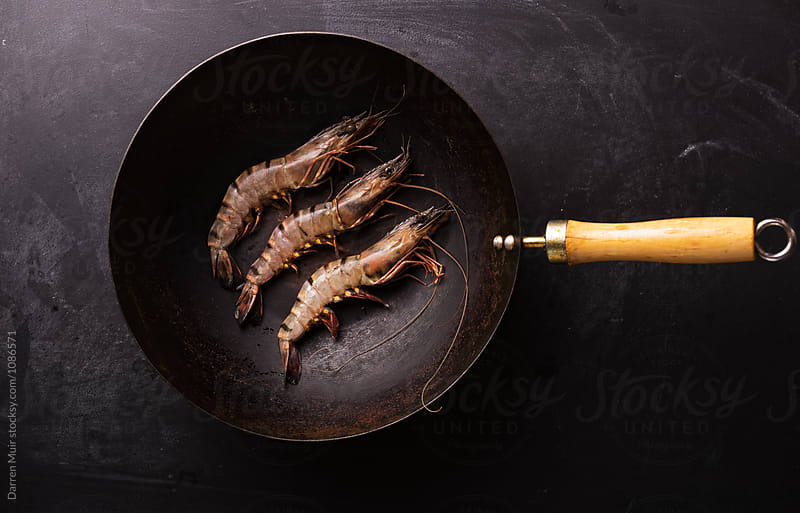 Tiger prawns in a wok on a dark background. by Darren Muir for Stocksy United