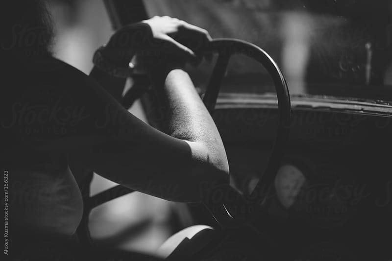 Woman sitting behind steering wheel of vintage car by Alexey Kuzma for Stocksy United