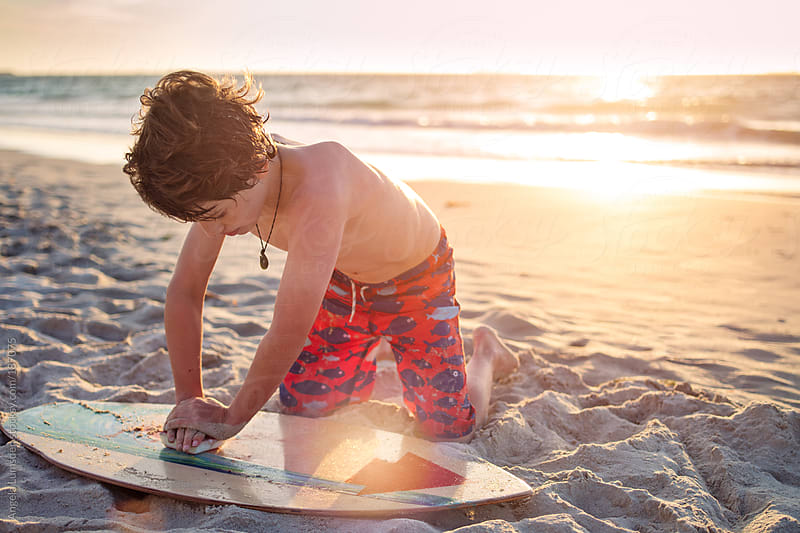 Boy waxing his skim board as the sun sets by Angela Lumsden for Stocksy United