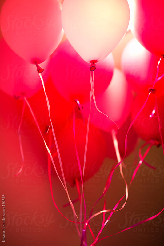Pink flying balloons attached to string by Lawren Lu for Stocksy United