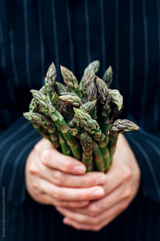 Young man holding fresh asparagus by Emoke Szabo for Stocksy United