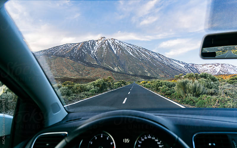 View of a snow covered mountain from inside a car by ACALU Studio for Stocksy United