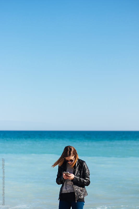 Young woman looking at mobile phone on the beach by Susana Ramírez for Stocksy United