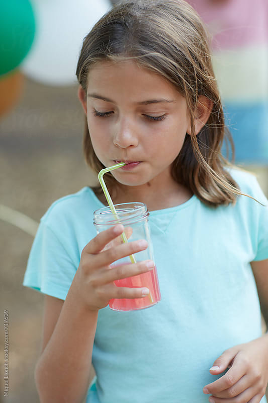 Young girl drinking a fruit beverage with straw by Miquel Llonch for Stocksy United