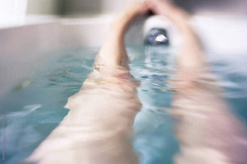 Woman's Legs in a Bathtub filled with Water by Holly Clark for Stocksy United