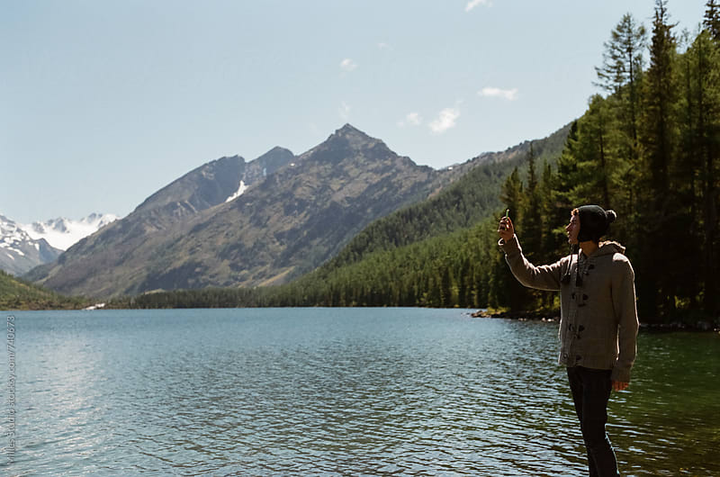 Young guy taking photo of mountains by Milles Studio for Stocksy United
