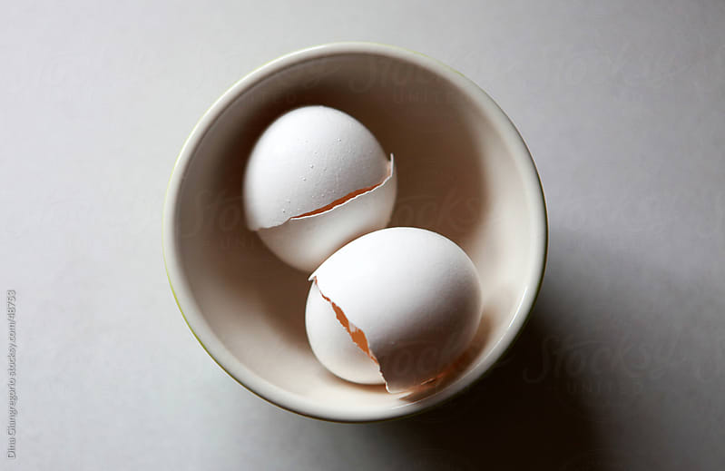 Top view of two cracked white eggs in a bowl by Dina Giangregorio for Stocksy United