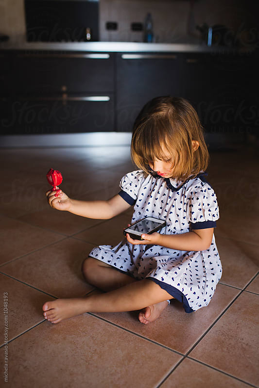 Sitting little girl eating ice cream and holding the cell phone by michela ravasio for Stocksy United