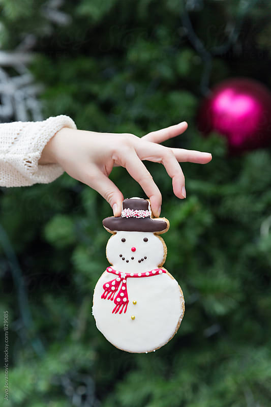 Woman holding a snowman cookie in front of a Christmas tree by Jovo Jovanovic for Stocksy United