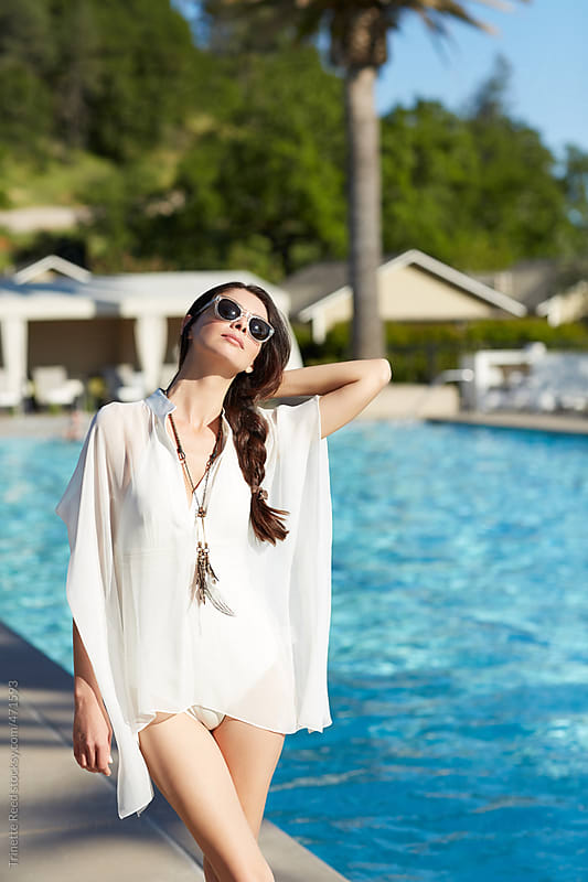Beautiful woman relaxing by the pool at luxury resort  by Trinette Reed for Stocksy United