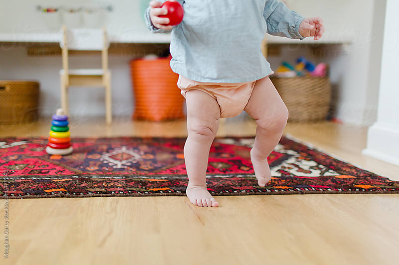 baby taking her first steps in a colorful room by Meaghan Curry for Stocksy United