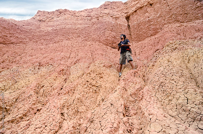 Photographer with his camera standing on almost vertical sand wall, bottom-up view by Alice Nerr for Stocksy United