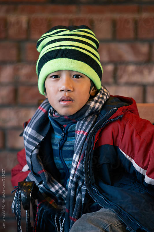 Portrait of a kid in winter clothes by Lawrence del Mundo for Stocksy United