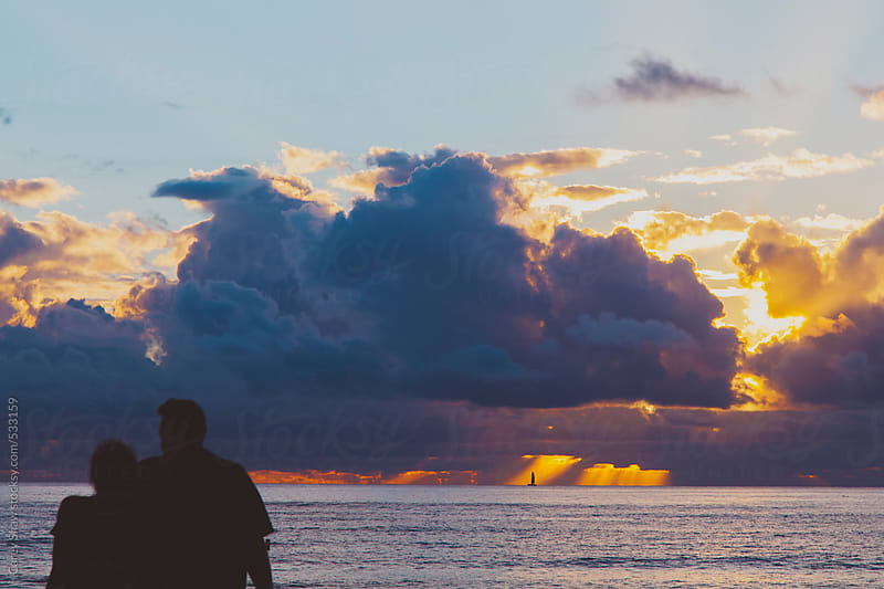 Silhouette of couple watching the ocean sunset by Carey Shaw for Stocksy United