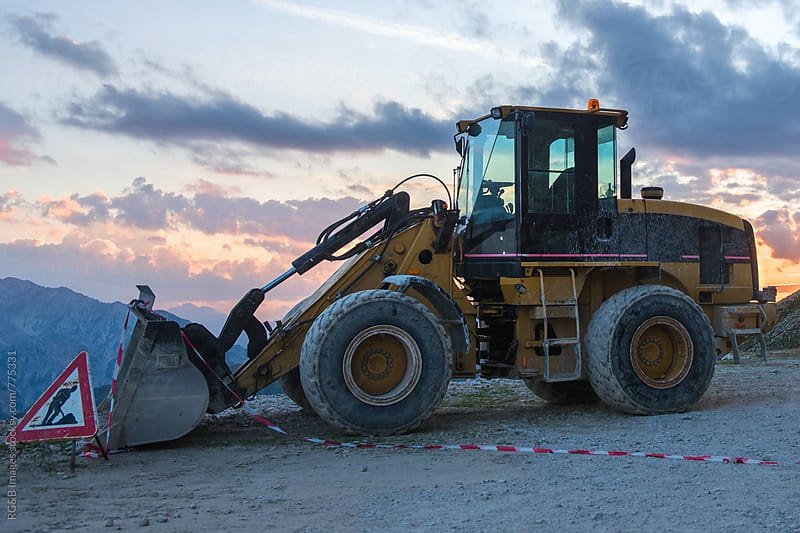 Bulldozer and men at work sign after working day outdoor by RG&B Images for Stocksy United