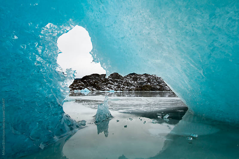 Opening in a blue iceberg on a frozen, ice-covered lake by Mihael Blikshteyn for Stocksy United