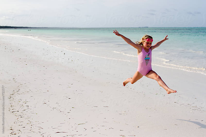 A little girl jumping athletically on a tropical beach by Helen Rushbrook for Stocksy United