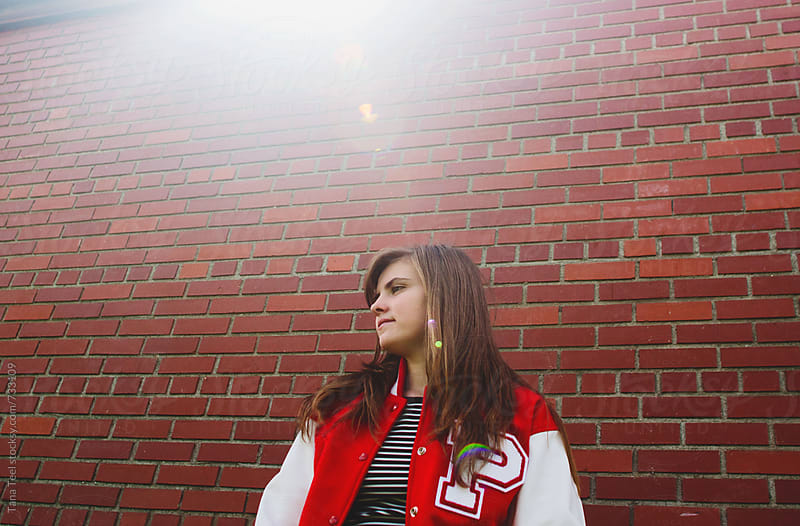 teenage girl in letterman jacket sits against brick wall by Tana Teel for Stocksy United