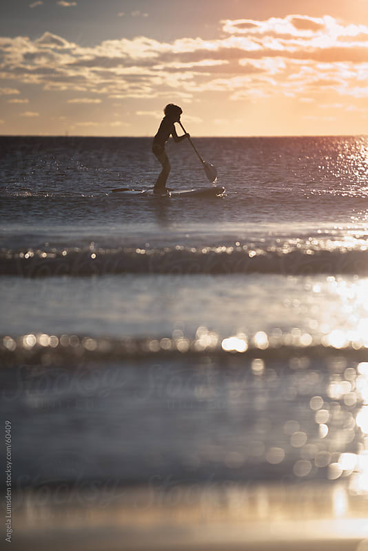 Small boy in silhouette paddling on a stand up board at sunset by Angela Lumsden for Stocksy United