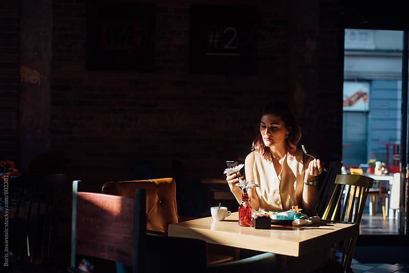 Young woman having a breakfast  by Boris Jovanovic for Stocksy United
