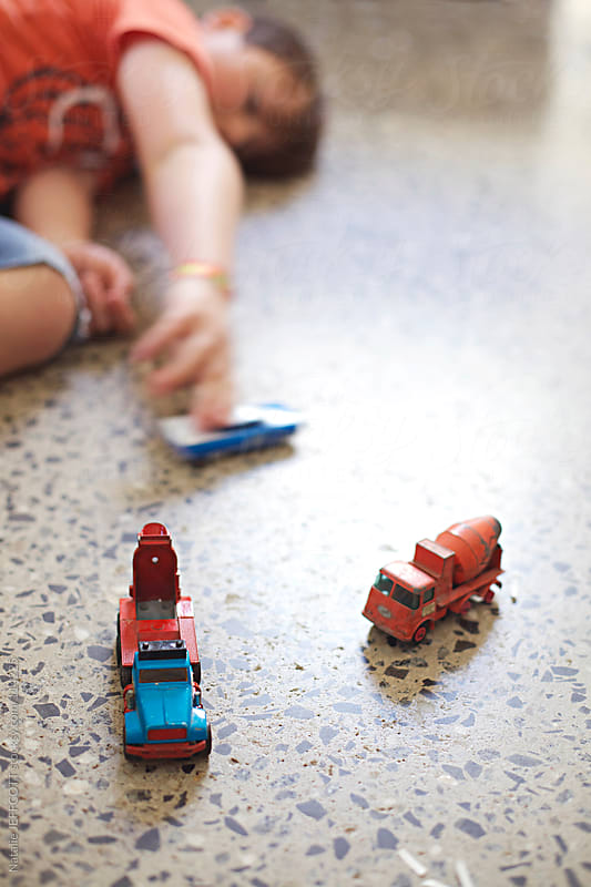 A young boy playing with toy cars and trucks by Natalie JEFFCOTT for Stocksy United