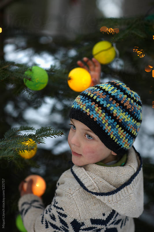 Child preparing the christmas tree with lights and ornaments by Miquel Llonch for Stocksy United