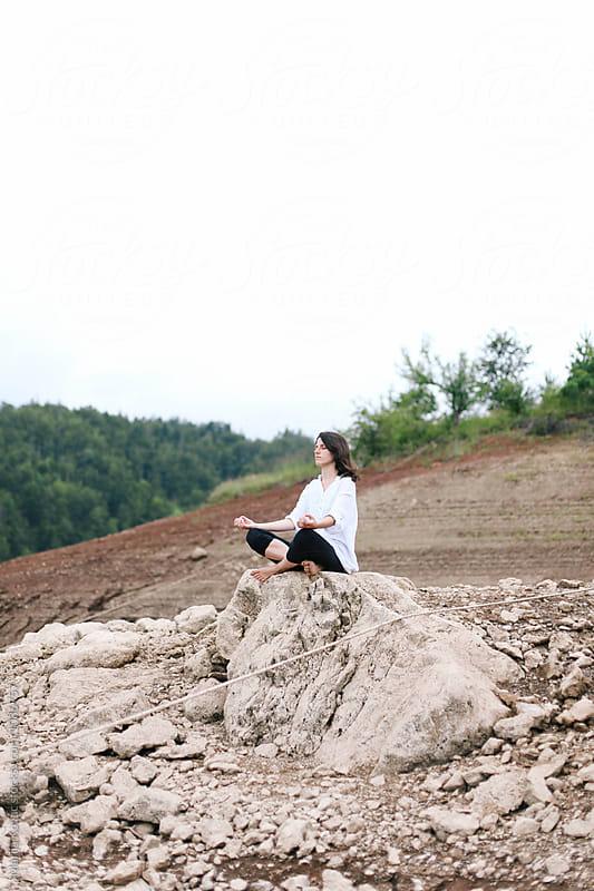 Woman meditating, sitting on the rock by Marija Kovac for Stocksy United