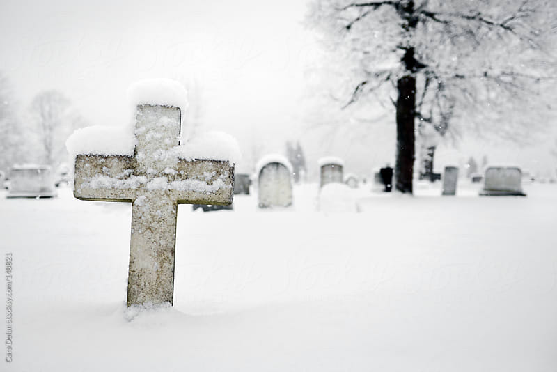 Cross gravestone in a snowy graveyard by Cara Dolan for Stocksy United