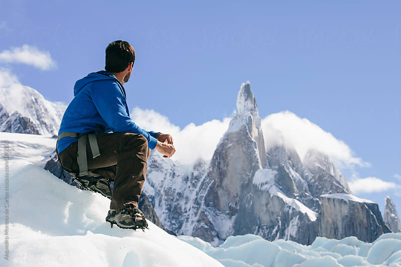 Young climber - hiker looking mountain on a glacier in Patagonia. Adventure travel by Alejandro Moreno de Carlos for Stocksy United
