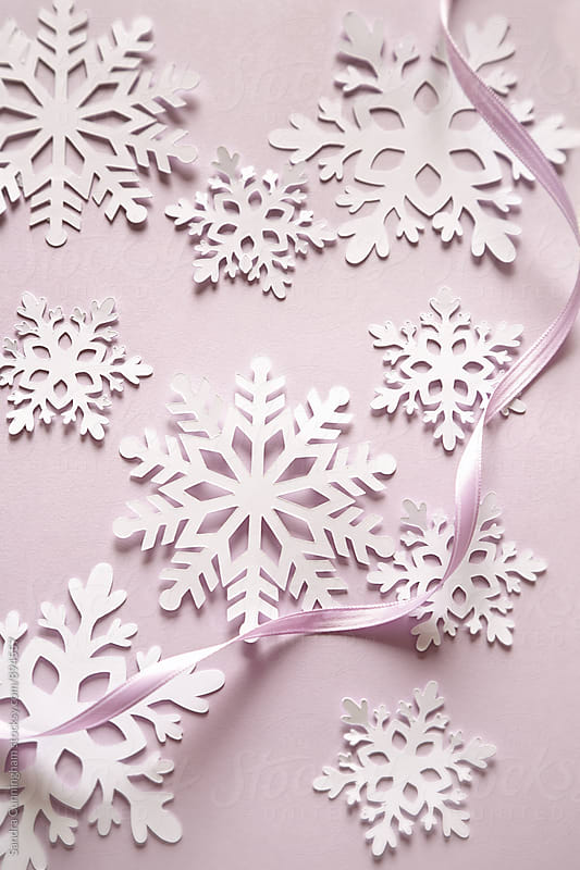 Paper snowflakes with ribbon for craft project by Sandra Cunningham for Stocksy United