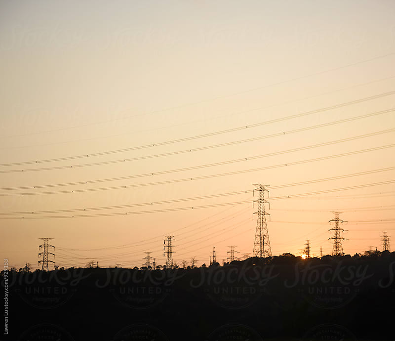 Electricity tower silhouetted on a rural hilltop at sunset by Lawren Lu for Stocksy United