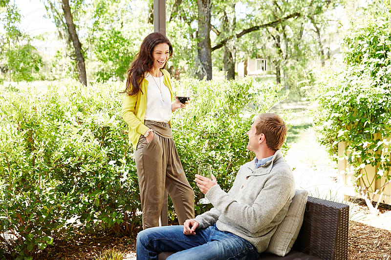 Beautiful couple relaxing with wine on back patio  by Trinette Reed for Stocksy United