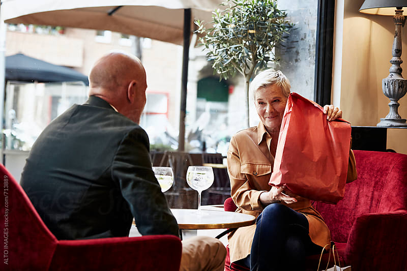 Senior Man Looking At Woman Holding Present In Restaurant by ALTO IMAGES for Stocksy United