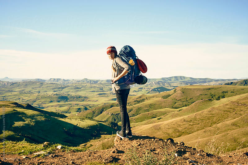 Female hiker with her back pack standing on the edge enjoying mountainous surroundings. by Jacques van Zyl for Stocksy United