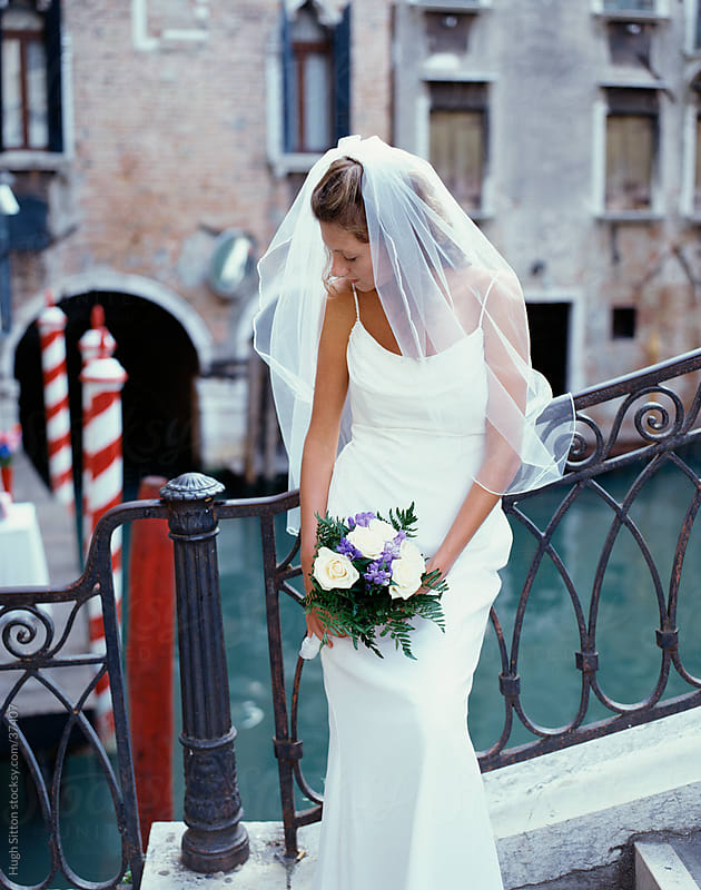 Bride in wedding dress standing next to the canals of Venice. by Hugh Sitton for Stocksy United